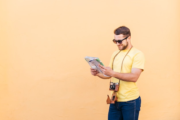Young male traveler photographer with camera around his neck reading map on peach background