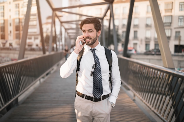 Young male traveler talking on cellphone