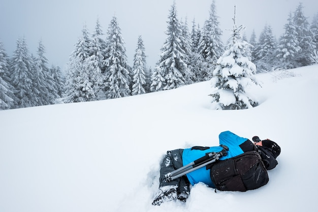 배낭을 가진 젊은 남성 여행자는 서리가 내린 겨울 날 안개를 배경으로 높은 눈 더미에서 아름 다운 키가 눈 덮인 전나무 나무의 사진을 찍습니다. 트레킹 및 여행 개념. 광고 공간
