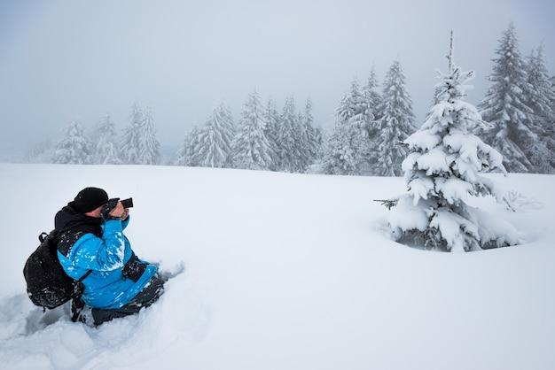 배낭을 가진 젊은 남성 여행자는 서리가 내린 겨울 날에 안개를 배경으로 높은 눈 더미에서 아름다운 키가 눈 덮인 전나무 나무의 사진을 찍습니다.