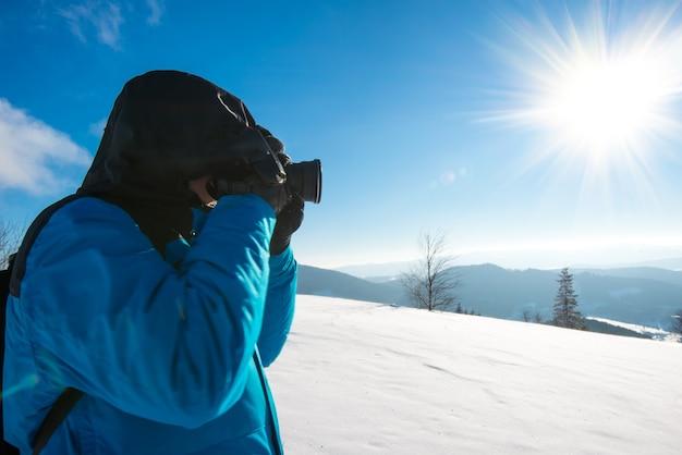 배낭을 메고 있는 젊은 남성 여행자는 높은 눈 더미에서 키 큰 눈 덮인 전나무의 사진을 찍는다