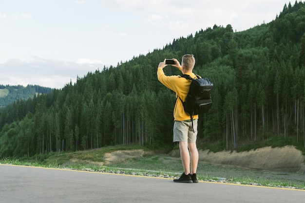 Young male traveler in yellow sweatshirt taking photo on smartphone of mountain forest landscape