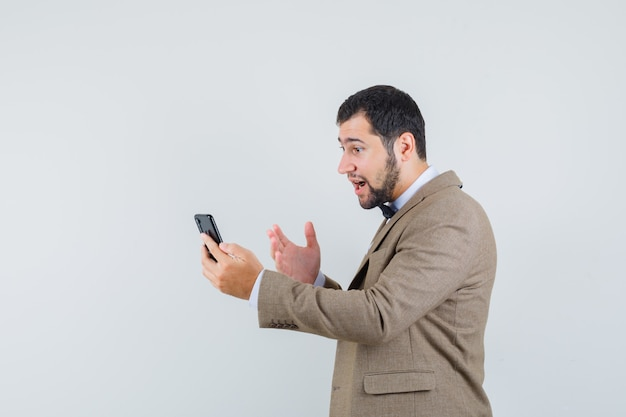 Young male trying to explain something on video chat in suit .
