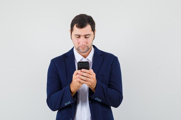 シャツに携帯電話を使用して若い男性