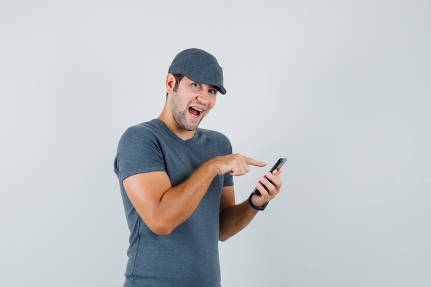 Young male using mobile phone in t-shirt cap and looking jolly