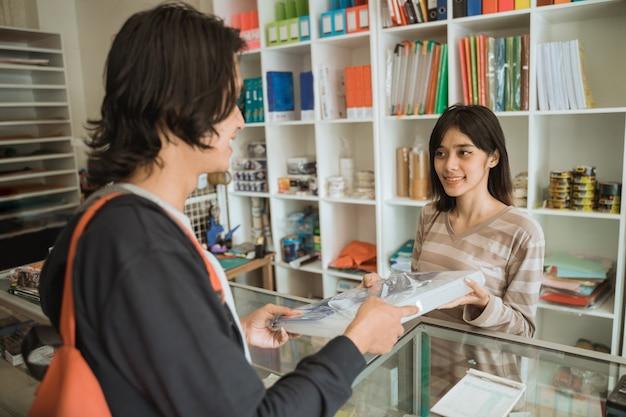Молодой мужчина посещает магазин канцелярских товаров, покупая канцелярские товары