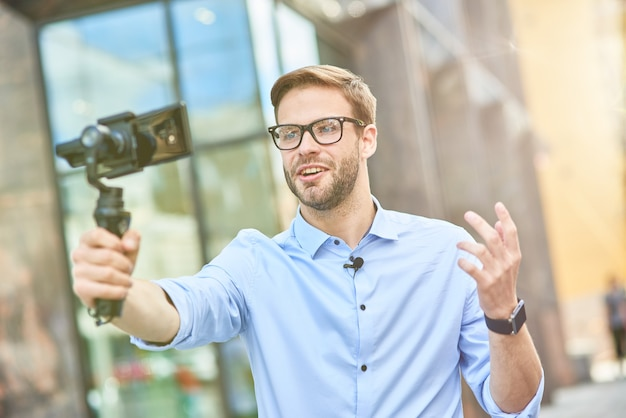 Young male vlogger wearing blue shirt and eyeglasses holding a gimbal with smartphone talking and