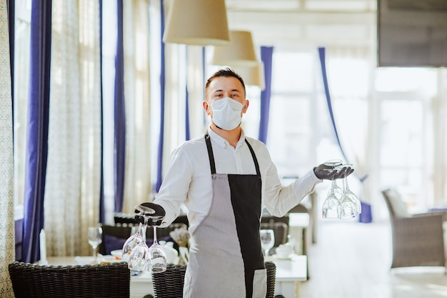 Young male waiter in medical mask, gloves and apron posing with bunch of wine glasses in restaurant.