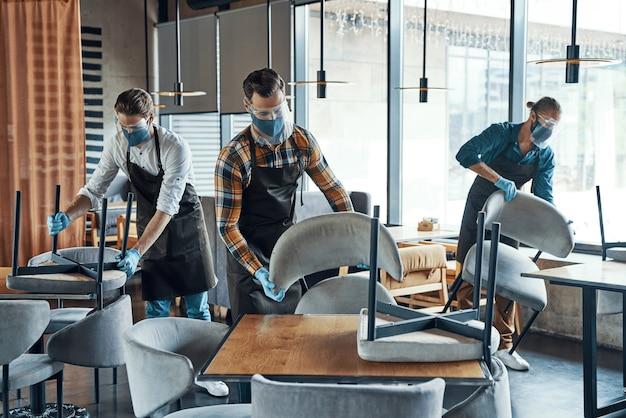 Молодые мужчины-официанты в защитной спецодежде расставляют мебель в ресторане