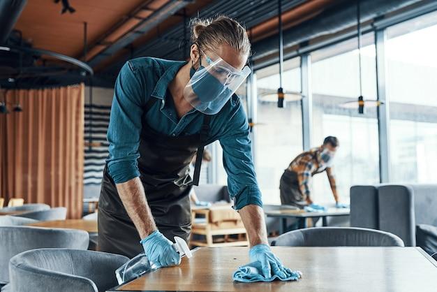 Молодые мужчины-официанты в защитной спецодежде чистят столы в ресторане