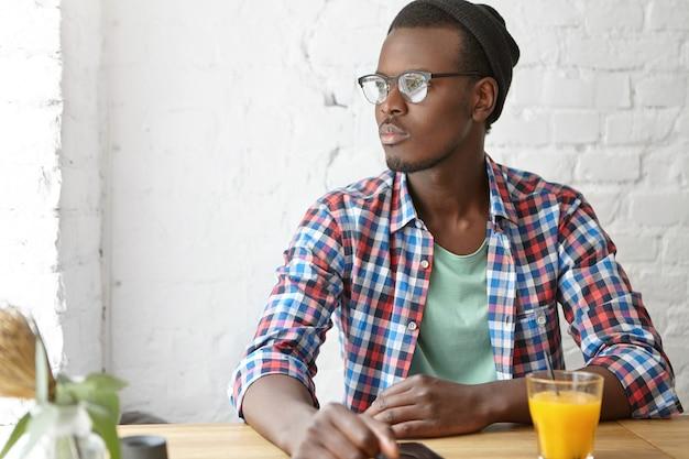 カフェで誰かを待っている若い男性