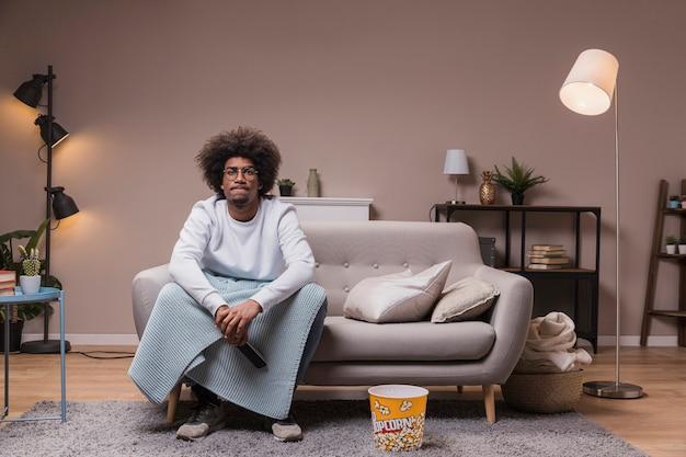 家でテレビを見ている若い男性
