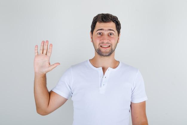 Молодой мужчина машет рукой в жесте приветствия в белой футболке и выглядит весело