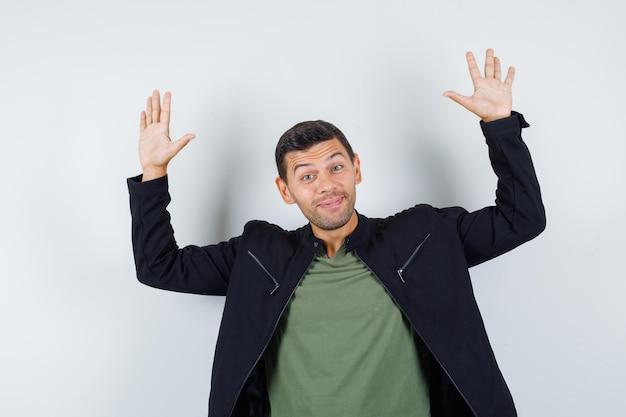 젊은 남성이 손을 흔들며 티셔츠, 재킷을 입고 밝은 표정으로 작별 인사를 합니다. 전면보기.