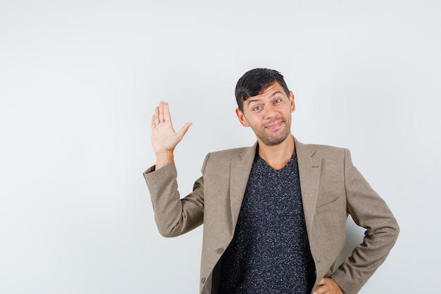 회색 갈색 재킷, 검은 셔츠 전면 보기에 작별 인사를 위해 손을 흔드는 젊은 남성.