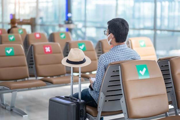 若い男性は空港ターミナルの椅子に座ってフェイスマスクを着用し、コロナウイルス感染症(covid-19)感染を防護し、流行に敏感な男性旅行者は旅行の準備ができています。新しい通常および社会的距離の概念