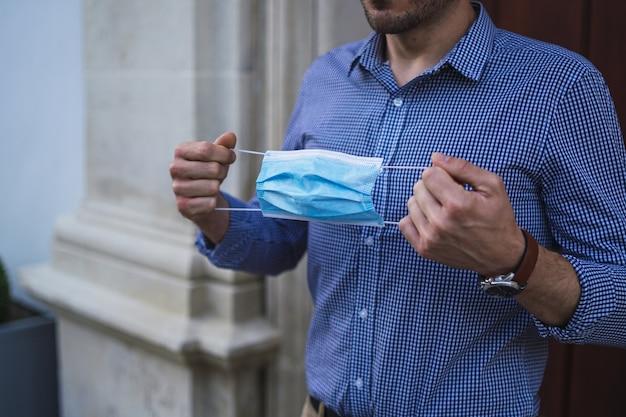 医療用フェイスマスクを保持しているゲートに立っている青いシャツを着た若い男性