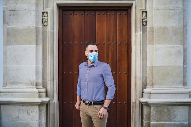 의료 얼굴 마스크-covid-19 개념으로 게이트에 서있는 파란색 셔츠를 입고 젊은 남성
