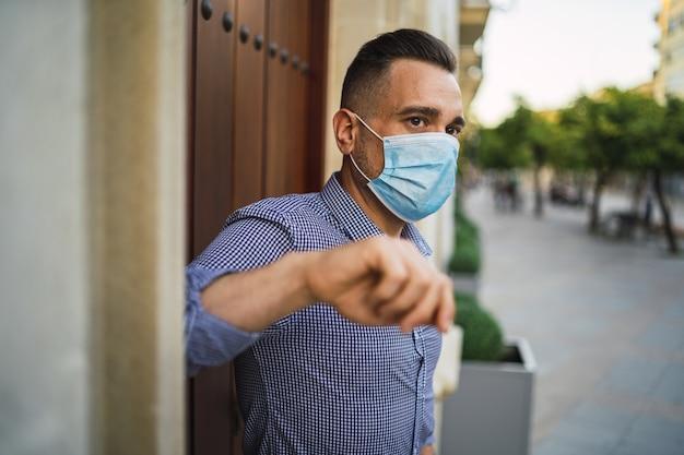 医療用フェイスマスクとゲートに立っている青いシャツを着た若い男性