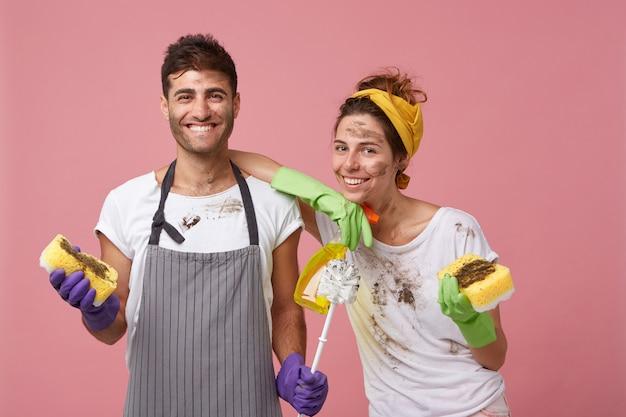 汚れた服を着たエプロンを身に着けている若い男性は、スポンジとブラシを持って広く笑っており、スポンジと洗剤を持って彼の肩に寄りかかってきれいな女性は、春の大掃除を終えて幸せです