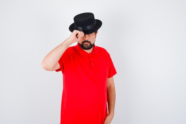赤いtシャツ、正面図で黒い帽子をかぶっている若い男性。