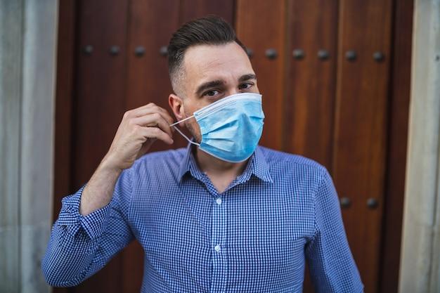 Giovane maschio che indossa una camicia blu in piedi al cancello con una maschera medica - concetto covid-19