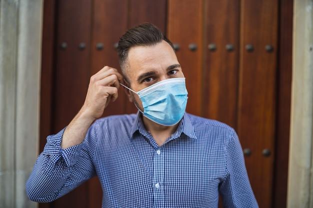 Giovane maschio che indossa una camicia blu in piedi al cancello con una maschera medica
