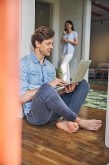집에 앉아있는 동안 회색 노트북에서 작업하는 캐주얼 옷을 입고 젊은 남성