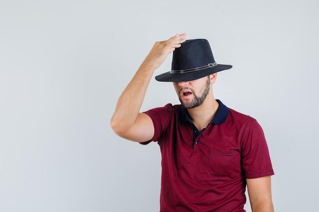 赤いtシャツを着た帽子をかぶって変な顔をしている若い男性。正面図。