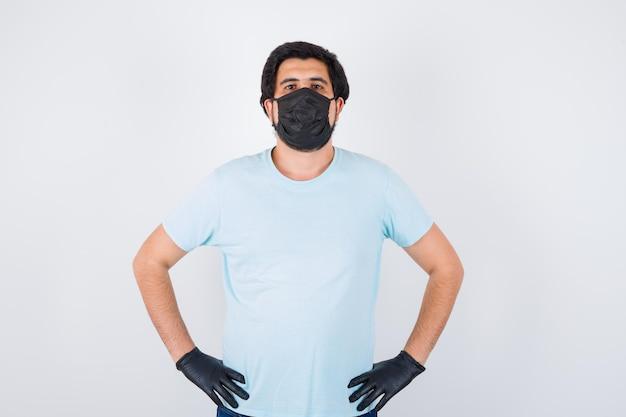 Giovane maschio che indossa maschera medica e guanti mentre si tiene per mano in vita in maglietta e sembra sicuro, vista frontale.