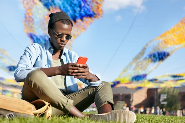 緑の芝生に座ってスタイリッシュな服を着ている若い男性