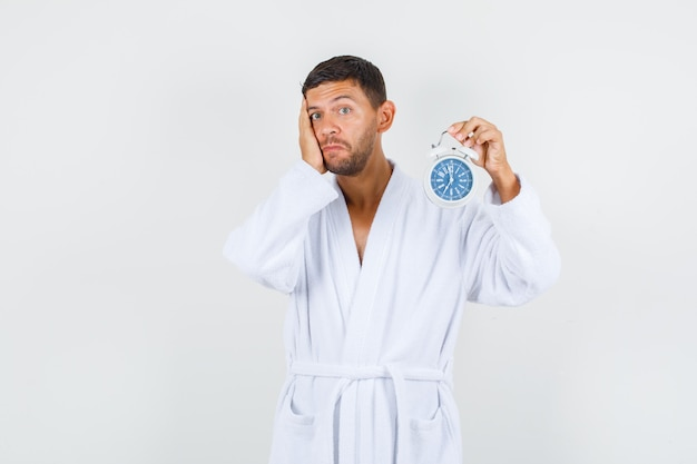 Young male in white bathrobe holding alarm clock and looking helpless , front view.