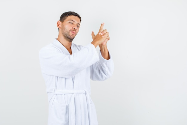 Young male in white bathrobe holding symbolic gun and looking confident , front view.