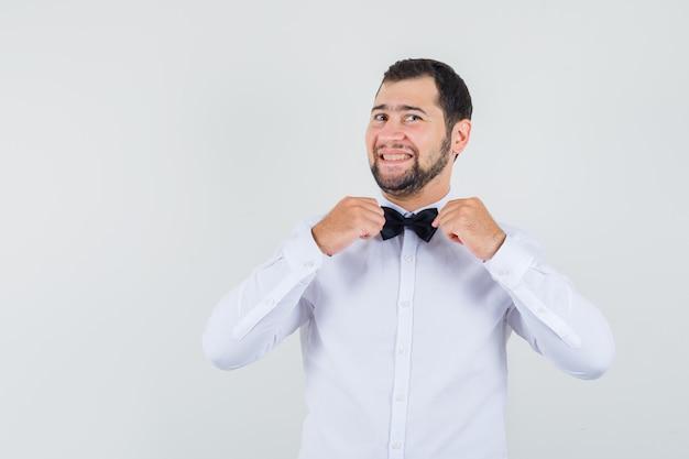Giovane maschio in camicia bianca che tiene la sua cravatta a farfalla e sembra allegro, vista frontale.