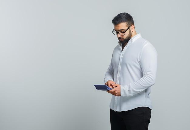 Giovane maschio in camicia bianca, pantaloni utilizzando la calcolatrice e guardando occupato