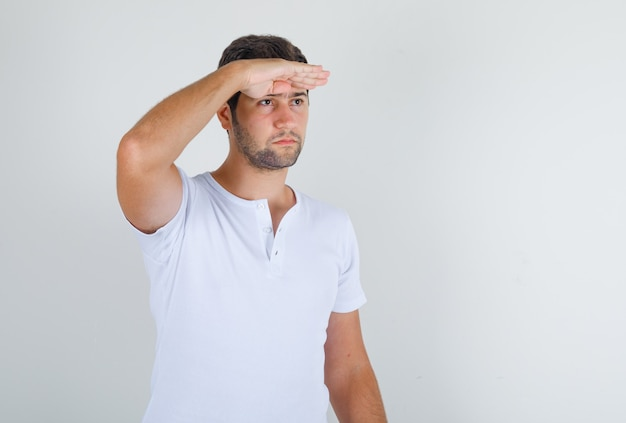 Young male in white t-shirt looking ahead with hand on forehead