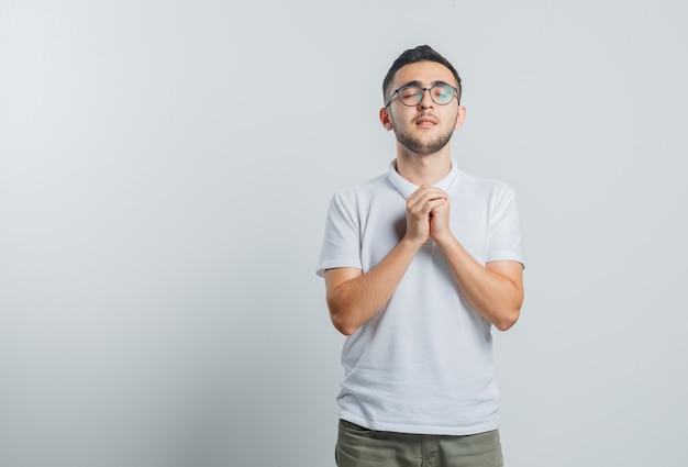 Young male in white t-shirt, pants clasping hands in praying gesture and looking hopeful