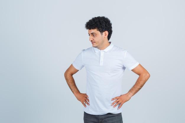 Giovane maschio in maglietta bianca, pantaloni che tengono le mani sulla vita e sembrano concentrati, vista frontale.