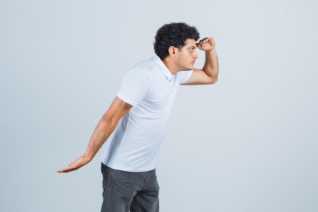 Giovane maschio in maglietta bianca, pantaloni che guardano lontano con la mano sopra la testa e sembrano concentrati, vista frontale.