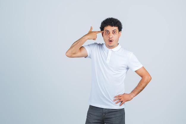Giovane maschio in maglietta bianca, pantaloni che fanno un gesto suicida e sembrano sorpresi, vista frontale.