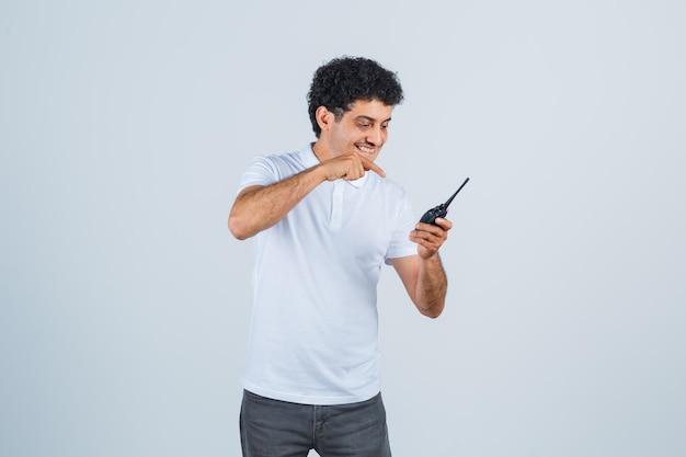Giovane maschio in maglietta bianca, pantaloni che puntano al telefono walkie-talkie della polizia e sembrano allegri, vista frontale.