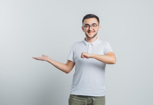 Giovane maschio in maglietta bianca, pantaloni che fingono di avere orologio, allargando il palmo da parte e guardando fiducioso
