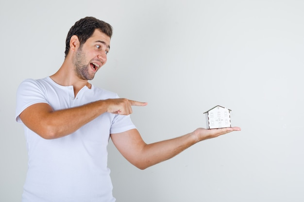 Young male in white t-shirt pointing finger at house model and looking cheerful