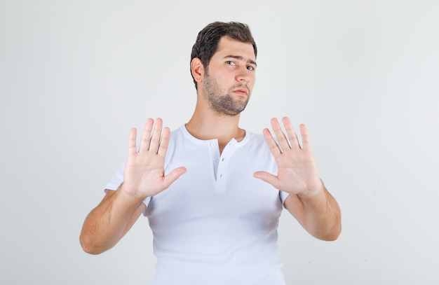 Young male in white t-shirt showing no sign and looking disgusted