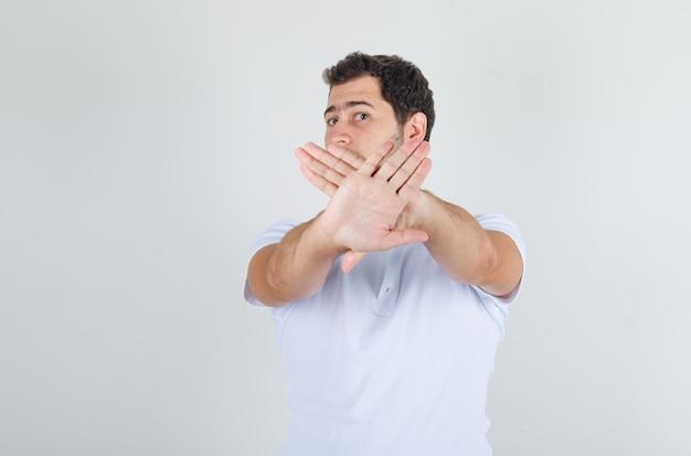 Giovane maschio in maglietta bianca che mostra il gesto di arresto e che sembra disgustato