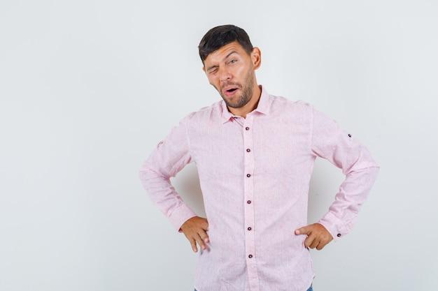 Молодой мужчина подмигивает руками на талии в розовой рубашке.