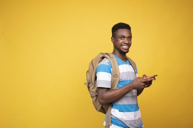 黄色の背景に彼の携帯電話を使用してバックパックを持つ若い男性