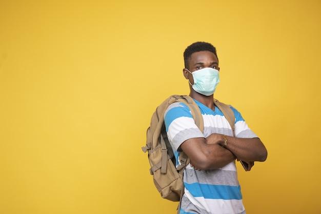 마스크를 쓰고 배낭을 메고 있는 젊은 남성