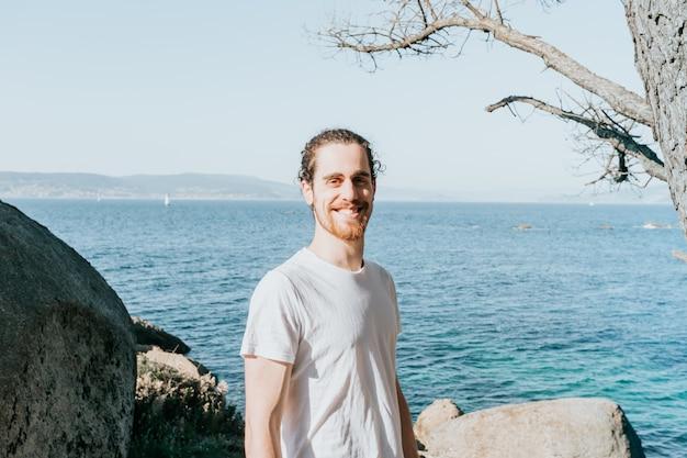 Молодой мужчина с пустой белой рубашкой, уверенно улыбаясь в камеру на побережье испании в пляжный день