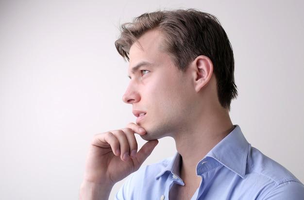 白い壁に立っている深い考えを持つ青いシャツを着た若い男性